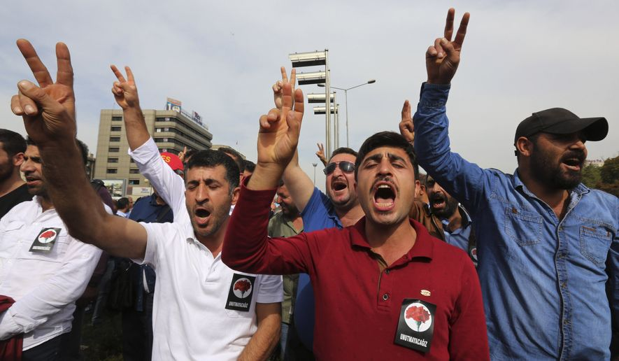 Protesters flash the V-sign and chant slogans as they protest Saturday's bombing attacks, during a rally in Ankara, Turkey, Sunday, Oct. 11, 2015. The twin explosions Saturday ripped through a crowd of activists rallying for increased democracy and an end to violence between Kurdish rebels and Turkish security forces, killing at least 95, and injuring scores of others, in Turkey's deadliest attack in years. (AP Photo/Burhan Ozbilici)