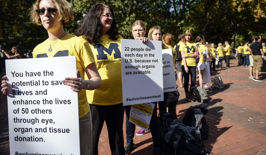 Stacy Brand, left, an employee of University of Michigan Transplant Center, holds a sign during a Wolverines Won't Wait event to raise awareness of life-saving donations Monday, October 12, 2015 in Ann Arbor, Mich. (Junfu Han | The Ann Arbor News)