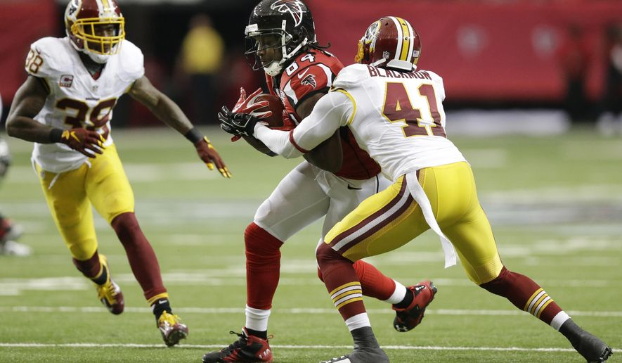 In this Sunday, Oct. 11, 2015 photo, Atlanta Falcons wide receiver Roddy White (84) makes a catch against Washington Redskins defensive back Will Blackmon (41) as Washington Redskins free safety Dashon Goldson (38) looks on during the second half of an NFL football game, in Atlanta. The Atlanta Falcons won 25-19 in overtime. (AP Photo/Brynn Anderson)