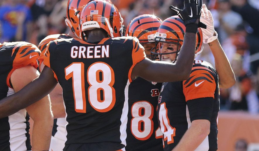 Cincinnati Bengals quarterback Andy Dalton, right, celebrates after scoring a touchdown in the second half of an NFL football game against the Seattle Seahawks, Sunday, Oct. 11, 2015, in Cincinnati. The Bengals won 27-24. (AP Photo/Gary Landers)