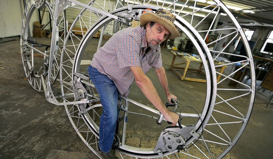 """In this Oct. 9, 2015 photo, artist Jim Avery sits on his bike called """"ABC2"""" in Dubuque, Iowa. The bike itself is about 6 feet tall and 13 feet long and weights in a little over 200 pounds. Avery, who suffers from colon cancer, has donated two mechanical sculptures to the city in hopes they'll inspire children. (Dave Kettering/TH Media via AP) MAGS OUT/TV OUT/MANDATORY CREDIT"""