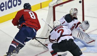 Washington Capitals left wing Alex Ovechkin (8), from Russia, watches as his goal gets past New Jersey Devils goalie Keith Kinkaid (1) during the third period of an NHL hockey game, Saturday, Oct. 10, 2015, in Washington. The Capitals won 5-3. (AP Photo/Alex Brandon)