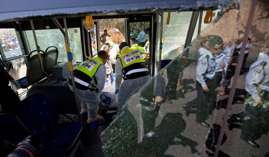 A pair of Palestinian men boarded a bus in Jerusalem and began shooting and stabbing passengers, while another assailant rammed a car into a bus station before stabbing bystanders. Two Israelis and one attacker were killed. (Associated Press)