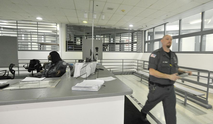 FILE - This March 17, 2015 file photo shows Detroit Detention Center Officers Kaether Jones, left, and Officer Don Pray  at the booking desk in the female side of the Detroit Detention Center in Detroit.   A policy requiring officers to be patted down before entering the state-run facility has been met with resistance from Detroit police. (Daniel Mears /Detroit News via AP)  DETROIT FREE PRESS OUT; HUFFINGTON POST OUT; MANDATORY CREDIT