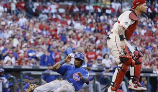 Chicago Cubs' Austin Jackson scores in front of St. Louis Cardinals catcher Yadier Molina during the second inning of Game 2 in baseball's National League Division Series Saturday, Oct. 10, 2015, in St. Louis. (AP Photo/Jeff Roberson)