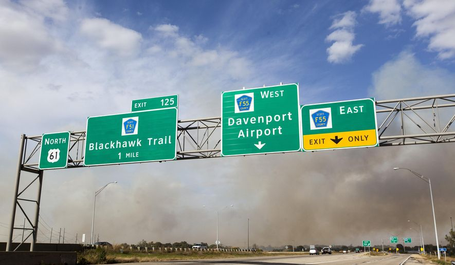 Smoke fills the sky looking north across Highway 61 from a field fire just north of the train tracks at S. 1st Street and E. Trail Rd. in Eldridge, Iowa, Monday, Oct. 12, 2015. (Louis Brems/Quad City Times via AP) MANDATORY CREDIT