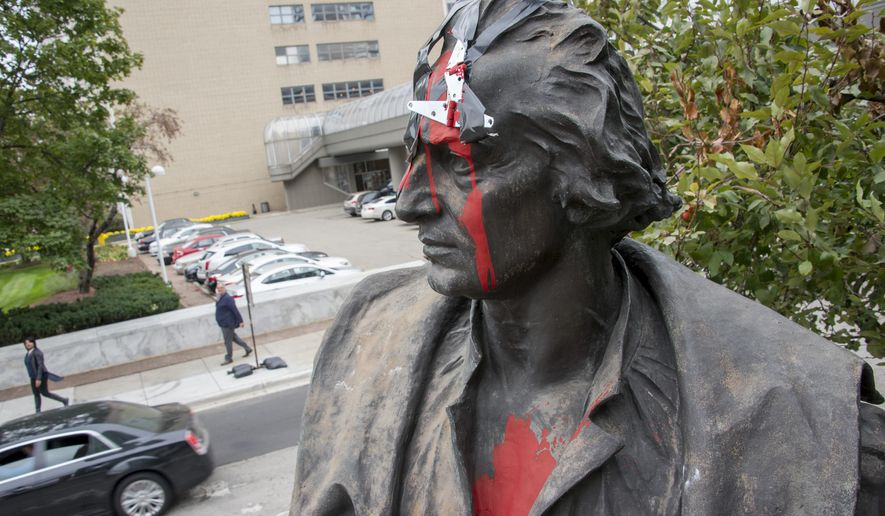 Red paint mars a statue of Christopher Columbus that stands on the corner of East Jefferson and Randolph streets in Detroit on Oct. 12, 2015 in Detroit.   The statue was vandalized with a hatchet affixed to the head and red paint. (David Guralnick/Detroit News via AP)  DETROIT FREE PRESS OUT; HUFFINGTON POST OUT; MANDATORY CREDIT