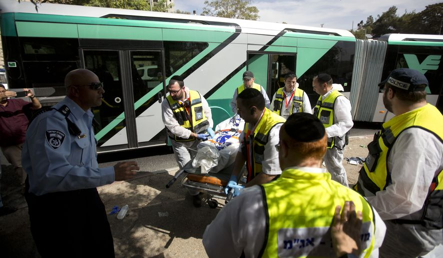 Israeli ZAKA emergency response members carry the body of an Israeli at the scene of a shooting attack in Jerusalem, Tuesday, Oct. 13, 2015. A pair of Palestinian men boarded a bus in Jerusalem and began shooting and stabbing passengers, while another assailant rammed a car into a bus station before stabbing bystanders, in near-simultaneous attacks that escalated a month long wave of violence. (AP Photo/Sebastian Scheiner)