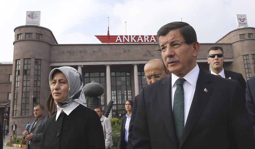 Turkish Prime Minister Ahmet Davutoglu and his wife Sare Davutoglu arrive to offer carnations at the site of an explosion in Ankara, Turkey, Tuesday, Oct. 13, 2015. Authorities in Istanbul banned a protest rally and march by the same trade union and civic society groups who lost friends and colleagues in Turkey's bloodiest terror attack. (Hakan Goktepe/Prime Ministry Press Service via AP, Pool)