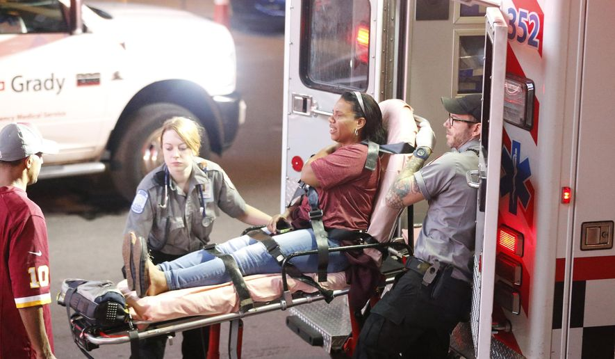 A woman is transported to a waiting ambulance after being injured inside the Georgia Dome on an escalator after an Atlanta Falcons football game according to a witness at the scene, Sunday, Oct. 11, 2015, in Atlanta. (AP Photo/John Bazemore)