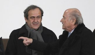 FIFA President Sepp Blatter, right, and UEFA President Michel Platini talk before the semi final soccer match between Real Madrid and Cruz Azul at the Club World Cup soccer tournament in Marrakech, Morocco, in this Dec. 16, 2014, file photo. On Thursday, Oct. 8, 2015, file photo FIFA provisionally banned President Sepp Blatter and UEFA President Michel Platini for 90 days. (AP Photo/Christophe Ena, file)