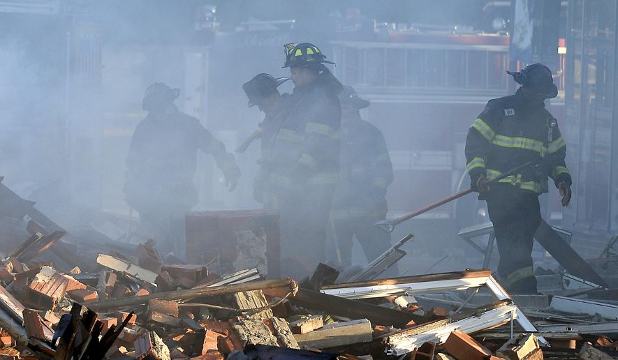 Kansas City firefighters look over the aftermath of a building fire Tuesday, Oct. 13, 2015 in Kansas City, Mo.   Two firefighters involved in rescuing two residents from a burning building died after a wall collapsed on them, authorities said. Fire Chief Paul Berardi said two other firefighters were injured Monday night as the massive fire engulfed the building comprising businesses and apartments on the city's northeast side.  (Keith Myers/The Kansas City Star via AP) MANDATORY CREDIT