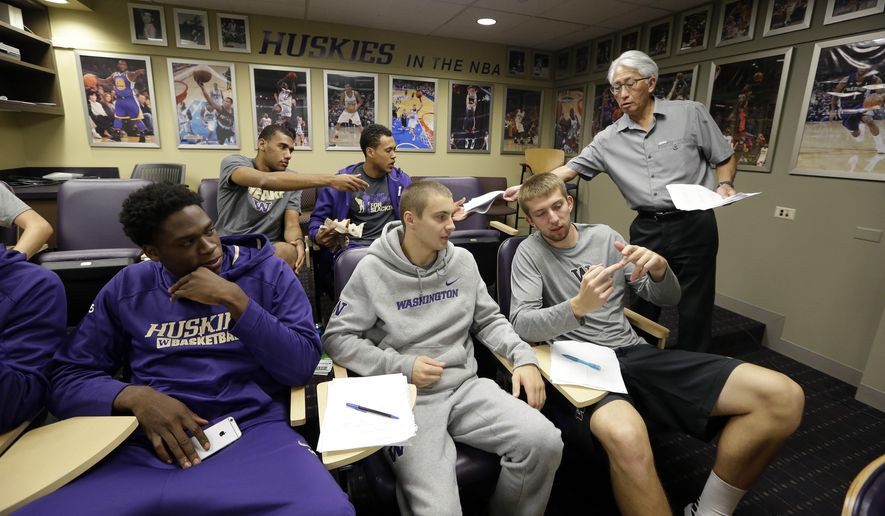 In this photo taken Sept. 28, 2015, professor Shawn Wong hands out papers to Washington men's basketball players during a class in Chinese culture in Seattle. In the front row are Noah Dickerson, left, Dan Kingma and Greg Bowman, and seated behind are Devenir Duruisseau and KJ Garrett. Washington is embarking on a unique journey to begin the 2015-16 basketball season. The team will fly to China to open the season against Texas in Shanghai, the first regular season college basketball game ever played in China. (AP Photo/Elaine Thompson)
