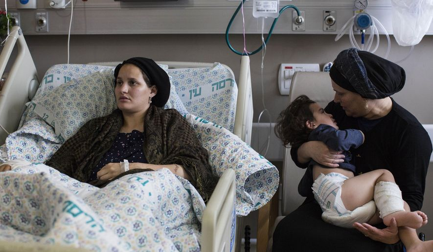 In this Monday, Oct. 12, 2015 photo, Odel Bennett lies on a bed as her mother Miriam Gal holds Odel's 2-year-old son Natan at the Hadassah Medical Center in Jerusalem. Bennett has been hospitalized since a Palestinian stabbed her husband Aharon to death on Oct. 3, seriously wounded her and lightly wounded Natan. She has learned that a Palestinian woman who stabbed an Israeli man in Jerusalem's Old City several days later was being treated four doors down the hall. (AP Photo/Tsafrir Abayov)