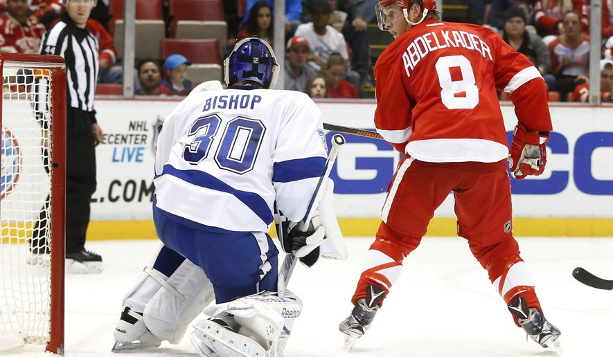 CORRECTS TO WATCHES A SHOT FROM DEFLECTS A SHOT - Detroit Red Wings left wing Justin Abdelkader (8) watches a Gustav Nyquist shot for a goal against Tampa Bay Lightning goalie Ben Bishop (30) in the second period of an NHL hockey game in Detroit Tuesday, Oct. 13, 2015. (AP Photo/Paul Sancya)