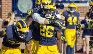 Michigan defensive back Jourdan Lewis (26) celebrates with teammates after scoring a touchdown on an interception in the second quarter of an NCAA college football game against Northwestern in Ann Arbor, Mich., Saturday, Oct. 10, 2015. (AP Photo/Tony Ding)