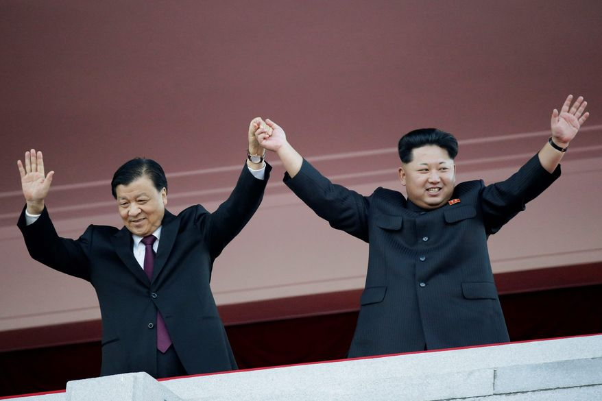 North Korean leader Kim Jong Un (right) waves alongside Chinese official Liu Yunshan during a military parade to mark the 70th anniversary of the North's ruling party and trumpet Mr. Kim's third-generation leadership in Pyongyang, North Korea. The two men raised their clasped hands above their heads like a pair of victorious athletes, as international media and tens of thousands of North Koreans looked on. The gesture during a high-profile celebration in Pyongyang seemed designed to scotch appearances that their countries have been drifting apart. (Associated Press)
