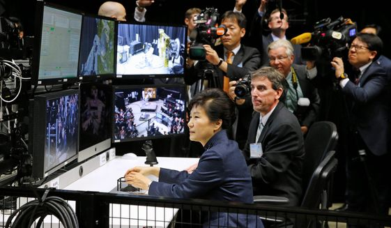 South Korean President Park Geun-hye operates a robotic arm during a tour of projects and programs that are underway at the agency's Goddard Space Flight Center, Wednesday, Oct. 14, 2015, in Greenbelt, Md. (AP Photo/Patrick Semansky)