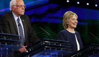 Hillary Rodham Clinton, right, smiles as Sen. Bernie Sanders, of Vermont, speaks during the CNN Democratic presidential debate Tuesday, Oct. 13, 2015, in Las Vegas. (AP Photo/John Locher)