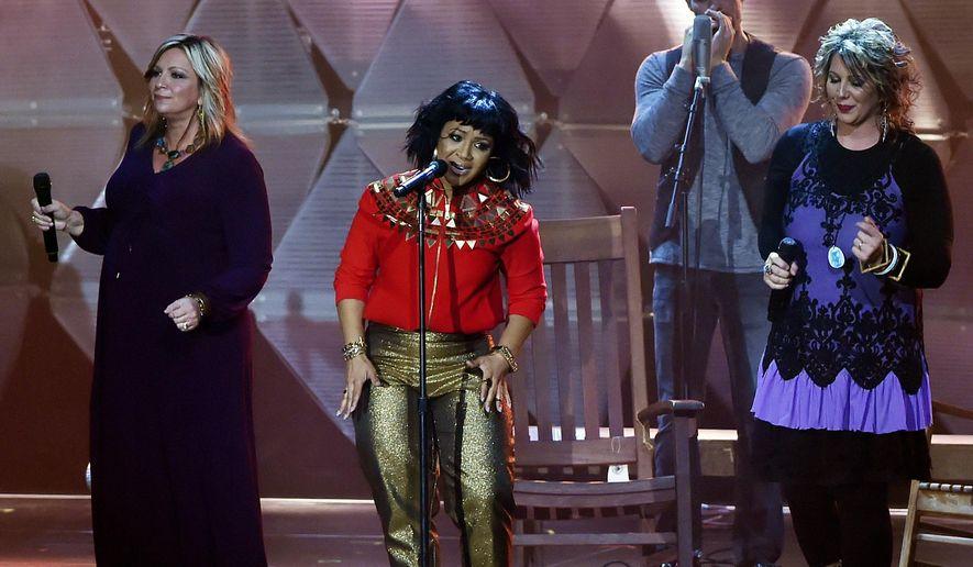 Erica Campbell, center, performs during the Dove Awards Tuesday, Oct. 13, 2015, in Nashville, Tenn. (AP Photo/Mark Zaleski)
