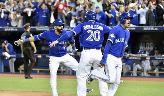 Toronto Blue Jays Jose Bautista, left, celebrates his three-run homer with teammates Ryan Goins, right, and Josh Donaldson (20) during the seventh inning in Game 5 of baseball's American League Division Series, Wednesday, Oct. 14, 2015 in Toronto. (Nathan Denette/The Canadian Press via AP) MANDATORY CREDIT