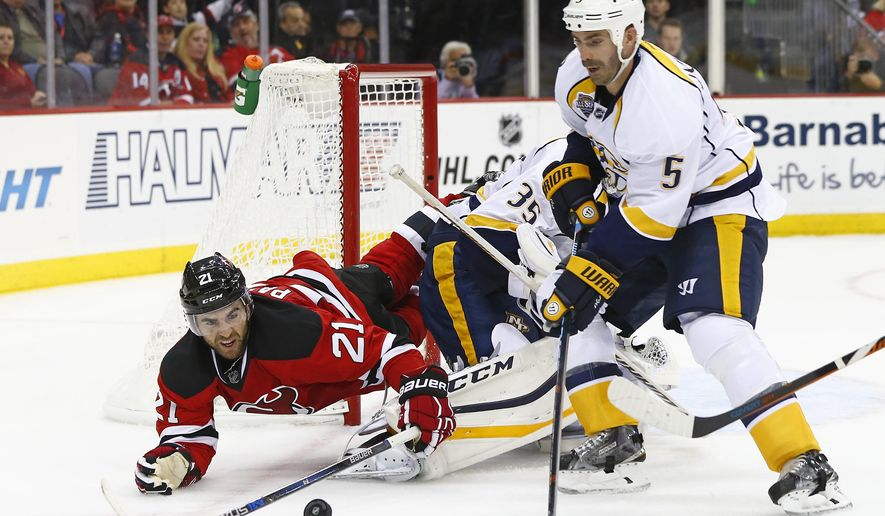 New Jersey Devils Kyle Palmieri (21) trips over Nashville Predators goalie Pekka Rinne (35) of Finland as he battles defensemen Barret Jackman (5) for the puck during the second period of an NHL hockey game in Newark, N.J., Friday, Oct. 13, 2015. (AP Photo/Rich Schultz)