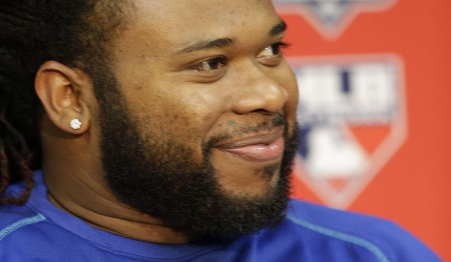 Kansas City Royals starting pitcher Johnny Cueto smiles during a news conference at Kauffman Stadium in Kansas City, Mo., Tuesday, Oct. 13, 2015. The Royals will play the Houston Astros Wednesday in the 5th baseball game of the ALDS. (AP Photo/Orlin Wagner)