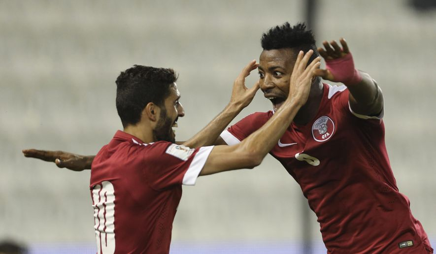 Qatar's Mohammed Kasola, right, celebrates with Hasan Al Haydos after scoring against Maldives during the 2018 FIFA World Cup, Group C, qualifying soccer match between Qatar and Maldives in Doha, Qatar, Tuesday, Oct. 13, 2015. (AP Photo/Osama Faisal)