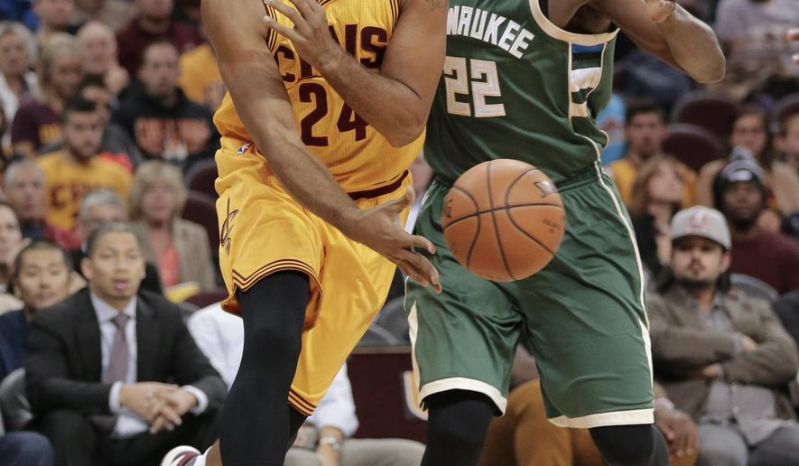 Cleveland Cavaliers' Richard Jefferson (24) passes around Milwaukee Bucks' Khris Middleton (22) during the first half of an NBA basketball game Tuesday, Oct. 13, 2015, in Cleveland. (AP Photo/Tony Dejak)