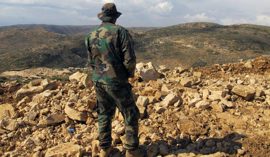 """A Hezbollah fighter looks toward Syria from the fields of the Lebanese border village of Brital. Iran is making its greatest progress to date toward its goal of creating a """"Shiite Crescent,"""" a land connection from Iran to Lebanon, where Tehran-backed Hezbollah militants have a long-established political foothold. (Associated Press/File)"""