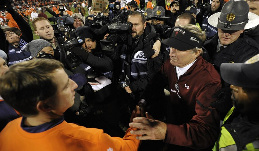 FILE - In this Nov. 24, 2012 file photo, South Carolina head coach Steve Spurrier, right, shakes hands with Clemson head coach Dabo Swinney after an NCAA college football game in Clemson, S.C.  South Carolina beats Clemson 27-17, allowing Spurrier to set a record with 65 wins. Spurrier also remains the winningest coach at Florida with 122 victories(AP Photo/Rainier Ehrhardt)