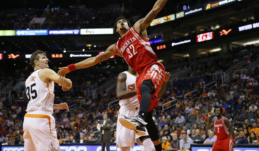 Houston Rockets' K.J. McDaniels (32) is fouled by Phoenix Suns' Mirza Teletovic (35), of Bosnia & Herzegovina, during the first half of an NBA preseason basketball game, Tuesday, Oct. 13, 2015, in Phoenix. (AP Photo/Matt York)