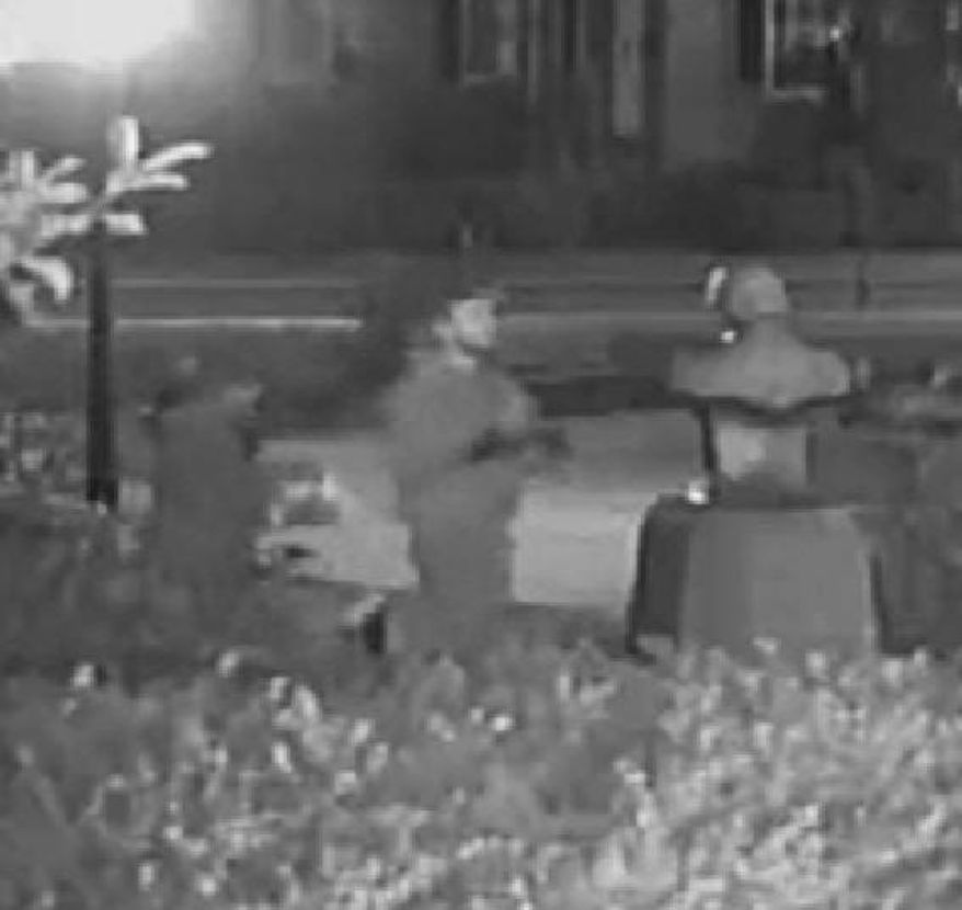 In this Oct. 11 2015, frame from surveillance video provided by the Frederick Police Department, the bust honoring Supreme Court justice Roger Brooke Taney is vandalized outside City Hall in Frederick, Md. Taney, whose bust was found covered in a red paint-like substance, wrote the 1857 Dred Scott decision affirming slavery. (Frederick Police Department via AP)