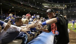 Chicago Cubs left fielder Kyle Schwarber gives high-fives to fans after the Cubs won 6-4 in Game 4 in baseball's National League Division Series against the St. Louis Cardinals, Tuesday, Oct. 13, 2015, in Chicago. (AP Photo/Nam Y. Huh)