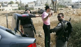 Israeli border police search a man driving out of the Palestinian neighborhood of Jabal Mukaber in Jerusalem, Wednesday, Oct. 14, 2015. Israel erected checkpoints and deployed several hundred soldiers in the Palestinian areas of the city Wednesday as it stepped up security following a series of attacks in Jerusalem. (AP Photo/Mahmoud Illean)