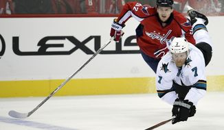 San Jose Sharks defenseman Paul Martin (7) reaches for the puck against Washington Capitals center Evgeny Kuznetsov (92), of Russia, during the first period of an NHL hockey game, Tuesday, Oct. 13, 2015, in Washington. (AP Photo/Nick Wass)