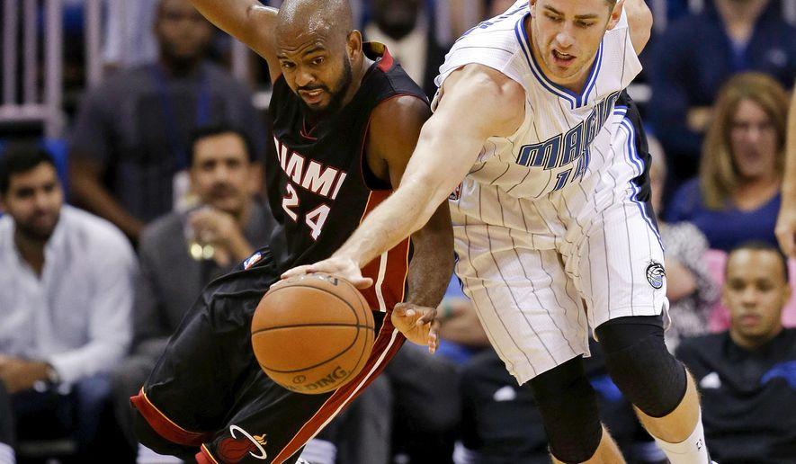 Miami Heat guard John Lucas III (24) and Orlando Magic forward Jason Smith, right, go after a loose ball during the first half of an NBA preseason basketball game, Tuesday, Oct. 13, 2015, in Orlando, Fla. (AP Photo/John Raoux)