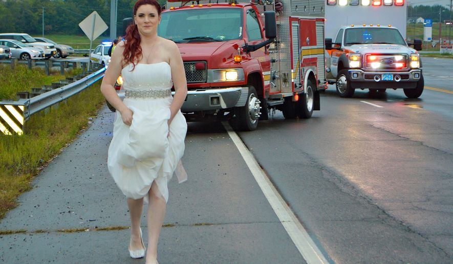 In this Oct. 3, 2015 photo provided by Marcy Martin Photography, her daughter Sarah Ray, in her wedding dress, attends to a car crash in Clarksville, Tenn. Ray's father and grandparents where in a car crash on their way to Ray's wedding reception. Ray, who is a paramedic, went to the scene to check on her relatives. (Marcy Martin Photography via AP) MANDATORY CREDIT
