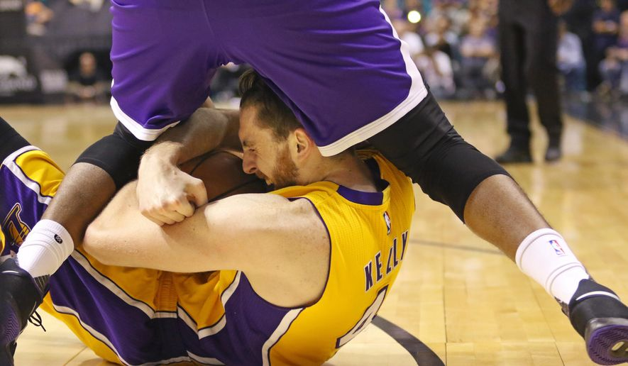 Los Angeles Lakers' Ryan Kelly, bottom, gets tangled with Sacramento Kings' Caron Butler during the first half of an NBA preseason game Tuesday, Oct. 13, 2015, in Las Vegas. (AP Photo/Ronda Churchill)