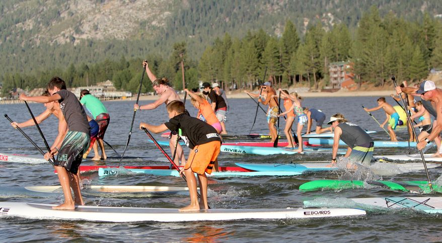 In this undated photo, paddlers participate in South Tahoe Standup Paddle's summer SUP Series on Lake Tahoe. Increased summer events and more resort offerings have been among the credits for higher summer lodging occupancy in western mountain towns from Colorado to California. (Anthony Gentile/The Tahoe Tribune via AP) MANDATORY CREDIT