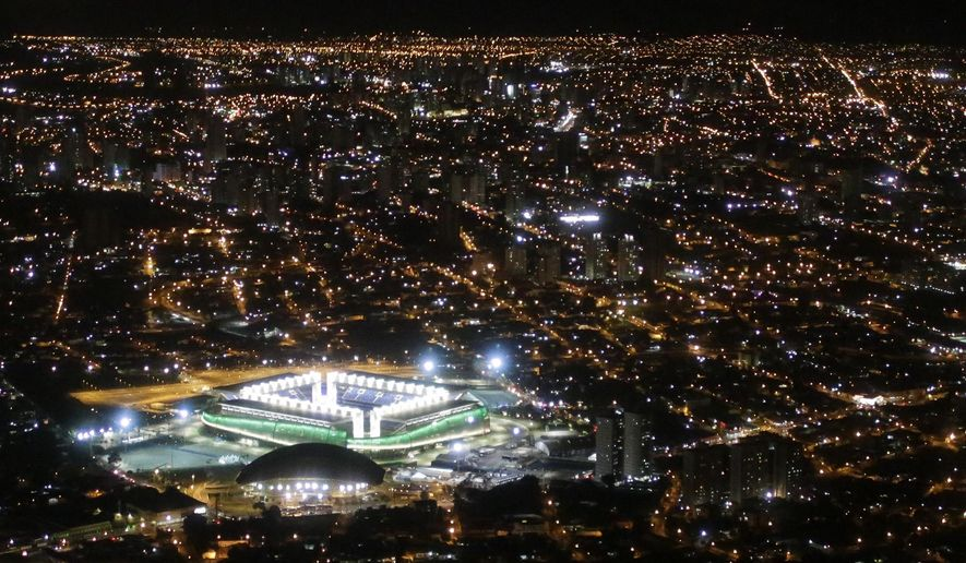 FILE - This night aerial, June 24, 2014, file photo, shows the illuminated Arena Pantanal where Japan and Colombia met up for their group C World Cup soccer match, in Cuiaba, Brazil. Two documentaries recently screened in Brazil on 2015, argue that hosting the World Cup was detrimental to the South American powerhouse. Taxpayers, the films show, ended up stuck with the bill for stadiums that cost several times their initial estimates. Some were built in cities such as the remote agricultural capital of Cuiaba, which does not have a first-division soccer team. (AP Photo/Felipe Dana, File)