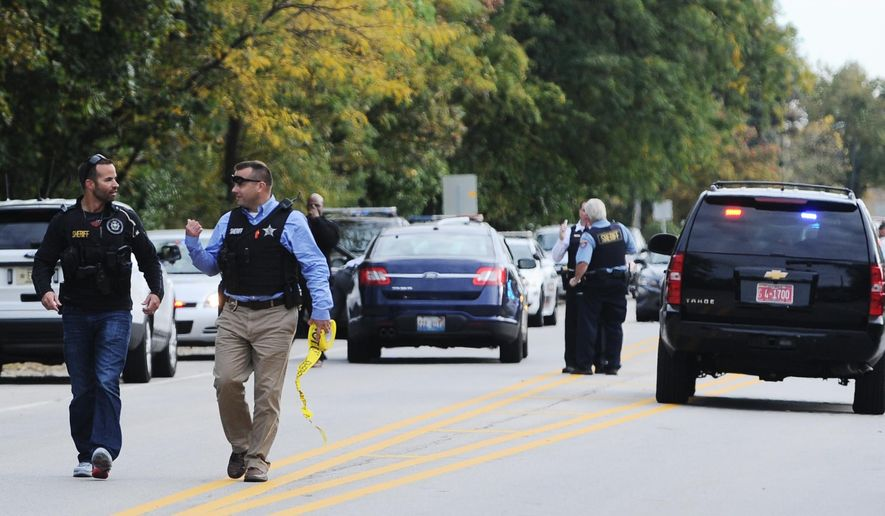 Law enforcement officials work the 43100 block of Lewis Avenue in Winthrop Harbor, Ill., where homicide suspect Andrew Obregon  was caught, Tuesday afternoon, Oct. 13, 2015. Kenosha County Sheriff David Beth said homicide  Obregon was in custody Tuesday after a foot chase near the Wisconsin-Illinois state line. No other details were immediately released. (Sean Krajacic/The Kenosha News via AP) MANDATORY CREDIT