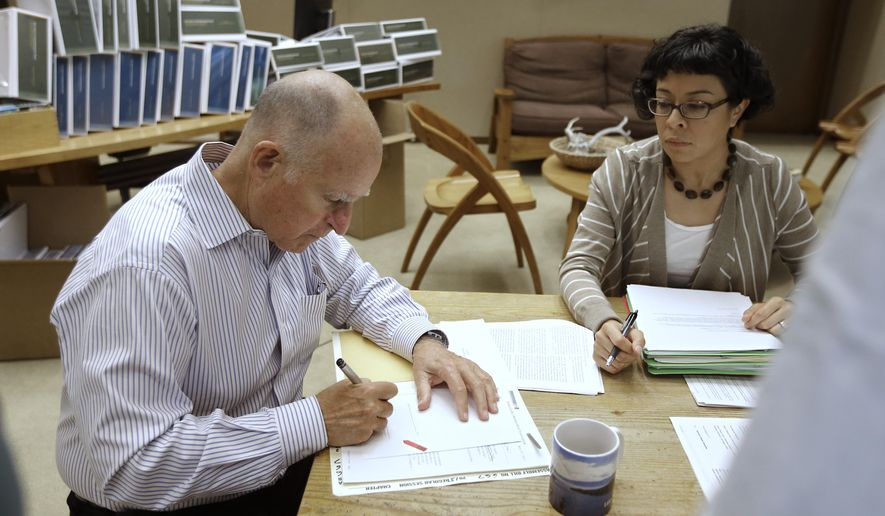 CORRECTS SPELLING OF FIRST NAME TO GRACIELA, INSTEAD OF GARCIELA - California Gov. Jerry Brown signs one of the hundreds of bills he has left to deal with as Graciela Castillo-Krings, right, his deputy legislative secretary, looks on at his Capitol office in Sacramento, Calif., Friday Oct. 9, 2015.  Brown has until Sunday to either sign, veto, or just let go into law the bills passed by lawmakers in the final days of this year's legislative session. (AP Photo/Rich Pedroncelli)