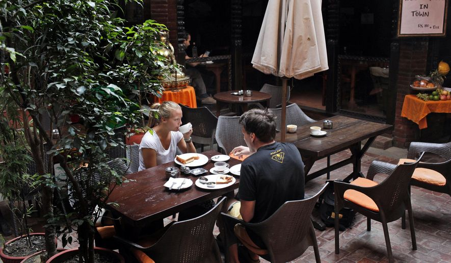 In this Tuesday, Oct. 13, 2015 photo, Norwegian couple Tom Omdal and Elise Skogheim eats breakfast at the popular New Orleans Restaurant in Thamel, the tourist hub in Kathmandu, Nepal. The restaurant was serving only a small number of items, none of which required much cooking even as many restaurants in Thamel have closed because they ran out of cooking gas.  Just when Nepal was recovering from the devastating earthquake that killed thousands, flattened hundreds of thousands of houses and chased away foreign tourists, protests by ethnic groups and severe fuel shortages are again keeping visitors away from the nation known for highest peaks in the world. (AP Photo/Niranjan Shrestha)