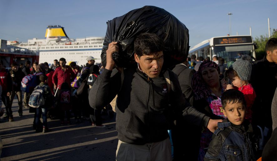 A man carries his belonging upon arriving with his family from the Greek island of Lesbos at the Athens' port of Piraeus Wednesday, Oct. 14, 2015. The international Organization for Migration said more than 593,000 people have crossed this year — of which 453,000 traveled from Turkey to Greece, which has faced a massive influx of people from Syria. (AP Photo/Petros Giannakouris)