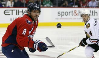 Washington Capitals left wing Alex Ovechkin (8), from Russia, attempts to hit the puck in the air with Chicago Blackhawks defenseman Niklas Hjalmarsson (4), from Sweden, behind, in the third period of an NHL hockey game, Thursday, Oct. 15, 2015, in Washington. The Capitals won 4-1. (AP Photo/Alex Brandon)