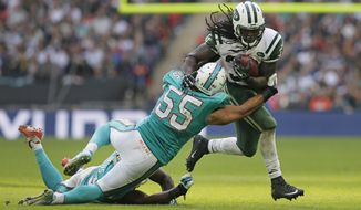 New York Jets' Chris Ivory, right, is tackled by Miami Dolphins' Koa Misi during the NFL football game between the New York Jets and the Miami Dolphins and at Wembley stadium in London, Sunday, Oct. 4, 2015. (AP Photo/Tim Ireland)