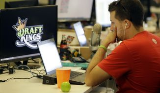 Devlin D'Zmura, a tending news manager at DraftKings, works on his laptop at the company's offices in Boston. (Associated Press)