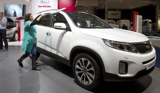 In this Jan. 10, 2013, file photo, a worker polishes the new Kia Sorrento during the Brussels Motor Show at the Expo Center in Brussels. Kia is recalling more than 377,000 Sorento SUVs because the transmission can be shifted out of park when the driver's foot isn't on the brake. (AP Photo/Virginia Mayo)