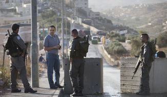 Israeli border police check Palestinian man ID next to newly placed concrete blocks in east Jerusalem neighborhood, Thursday, Oct. 15, 2015. Israel erected checkpoints and deployed several hundred soldiers in the Palestinian areas of the city Wednesday as it stepped up security following a series of attacks in Jerusalem. (AP Photo/Oded Balilty)